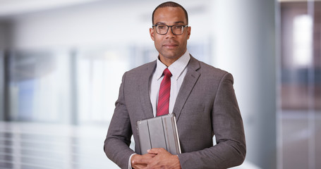 A black business professional poses for a portrait with his tablet and glasses. An African American executive stands with his pad while adjusting his spectacles