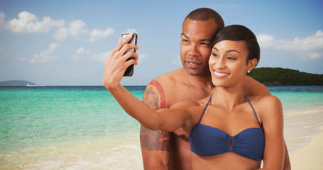 A black couple embrace each other and take a selfie on the beach. An African American man and woman take a picture on the shore