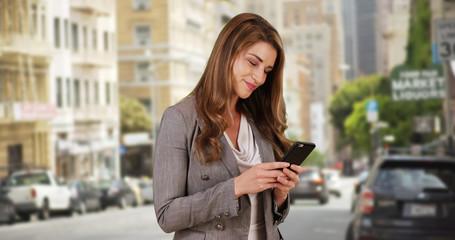 Cute Businesswoman intern using smartphone to communicate team members remotely. Woman in her 20s sending her team a message after leaving the office