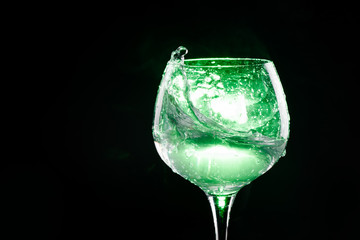 Splashing water in the wine glass with green background