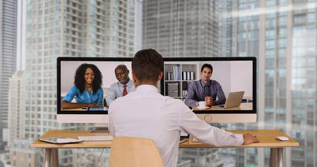 Successful group of business associates having internet based web conference over video chat. Black Hispanic and Caucasian team of office workers communicate using modern technology