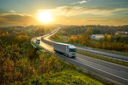 Silver trucks driving on the highway winding through forested landscape in autumn colors at sunset