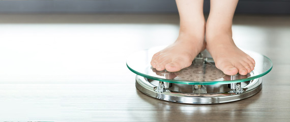 Feet of a young woman measuring her weight on a bathroom scale