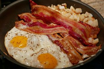 Amerikanisches Frühstück mit zwei Spiegeleiern, Schinkenspeck und Bratkartoffeln in Bratpfanne