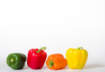 Four bell peppers in a row isolated on white background