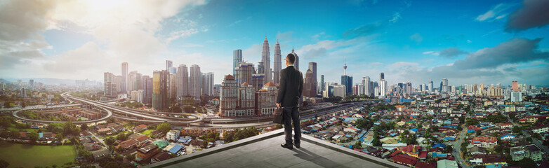 Businessman stand at rooftop looking great cityscape view and thinking business plan of the future .