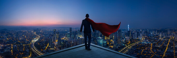 Businessman in suit and cape hero stand at rooftop looking great cityscape view and thinking business plan of the future . Night scene . Wall mural
