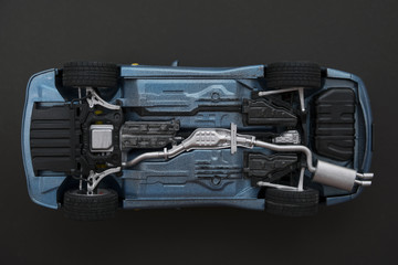 inverted car on a black background. bottom view of car