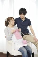 編み物をする妊婦と見守る夫