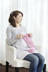 窓辺で編み物をする妊婦