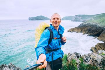 Smiling backpakcer traveler take selfie photo on ocean coast