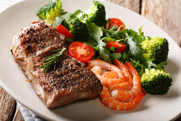 Beef steak with prawns and broccoli, tomatoes, arugula closeup on plate. Horizontal.  Surf and Turf