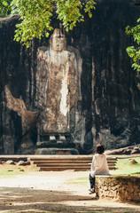 Woman looks on Buduruwagala - oldest Buddha statue in Sri Lanka (cca 1000 years old)