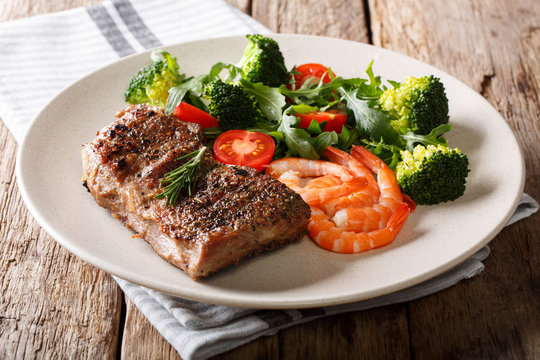 Delicious grilled beef steak with prawns and broccoli, tomatoes, arugula closeup on a plate. Surf and Turf. horizontal