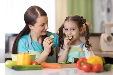 Cute child tasting vegetables as she prepares a meal with their mother in the kitchen