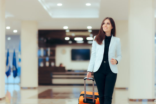Elegant Business Woman with Travel Trolley Luggage in Hotel Lobby