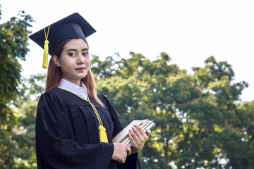 student graduate holding book in the garden