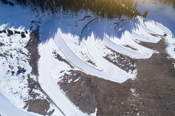Aerial view of the curving alpine skiing and snowboarding piste in mountains