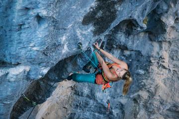 Blonde girl climbs tufa rock, Chitdibi, Turkey
