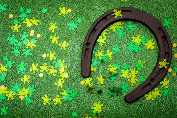 Lucky charm meme, st patricks day and luck of the irish concept with a rusty horseshoe covered party confetti against a sparkly green background