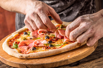 Pizza and Chef. Chef in the restaurant prepares a pizza and decorates it with  prosciutto