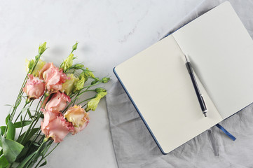 Open notebook with flowers on white marble