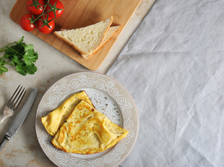 scrambled eggs on a plate, parsley, tomatoes, toast and textile napkin