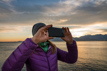 Girl takes photo of sun set and sea by her smartphone
