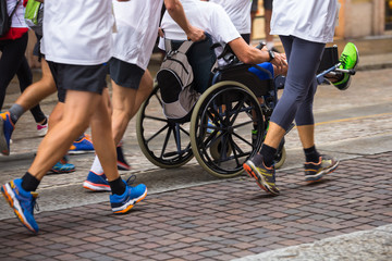 Disabled Athlete in a Sport Wheelchair during Marathon Helped by Runners