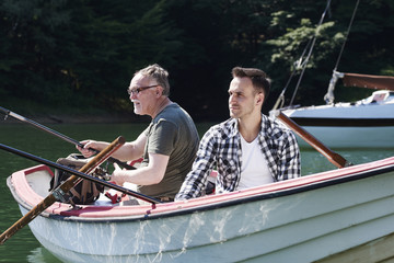 Focused men with fishing rod sitting on boat