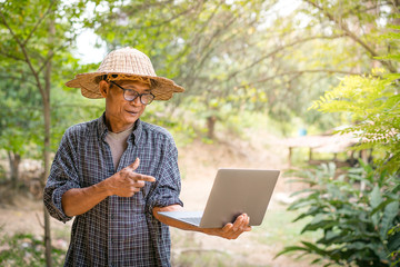 Farmer Asian with smartphone and laptop,Business and technology concept.