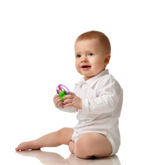 Infant child boy toddler sitting with plastic toy isolated