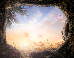 Easter Sunday concept: Empty tomb stone with palm leaves over meadow sunset background