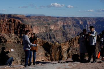 Visitors take pictures at Eagle Point on the west rim of the Grand Canyon