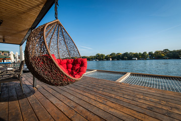 Hanging chair on terrace of log cabin