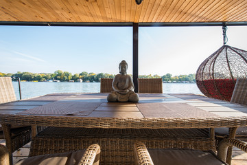 Buddha sculpture on table on balcony by river