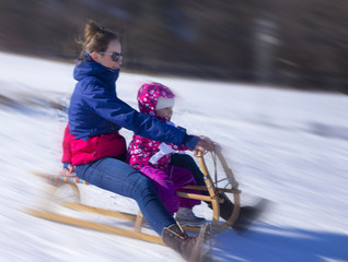 Mummy is sledging with her baby