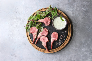 Grilled sliced rack of lamb with yogurt mint sauce served with green salad young beetroot leaves and pink salt on round wooden slate board over grey texture background. Top view, space