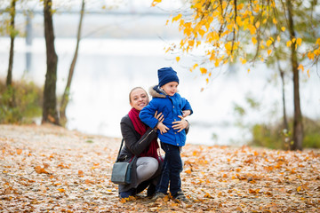 Mother and sun having fun at sunset in autumn near the river. A happy family and active lifestyle concept