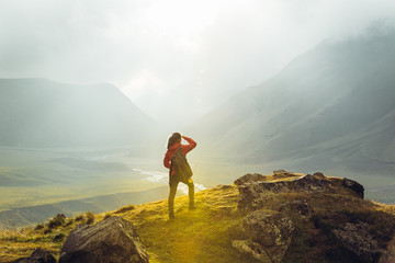 Discovery Travel Destination Concept. Hiker Young Woman With Backpack Rises To The Mountain Top Against Backdrop Of Sunset, Rear View
