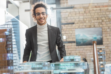happy young architect in suit near buildings miniature model at office