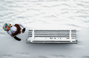 A woman takes a picture of a snow covered bench in a park in Lausanne