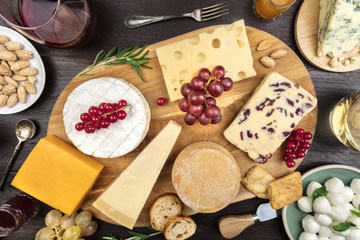Various types of cheese with wine on rustic background