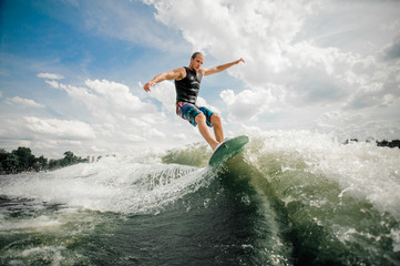 Young and active man wakesurfing on the board down the river Wall mural
