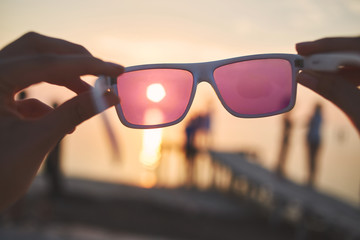 view of the sun, sea and sky through pink sunglasses