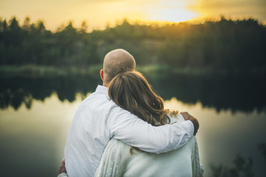 couple is hugging looking to the sunset sitting close up