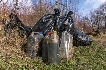 Illegal dumping of hazardous waste such as waste oil, building materials and other things in nature. Concept: crime or environmental protection