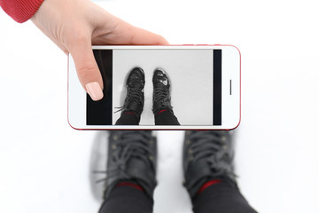 Stylish woman taking picture of her warm shoes on snowy winter day