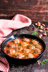 Cooking pan with meatballs in tomato sauce with spices and almond nuts on a wooden table, selective focus. Image with copy space. Meatballs are made of minced pork and beef meat. American food.