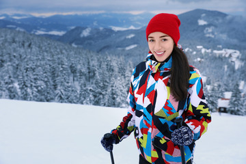 Beautiful woman on ski piste at snowy resort. Winter vacation